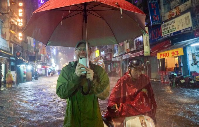 Tourists enjoy heavy downpours, flooding in Saigon - 2