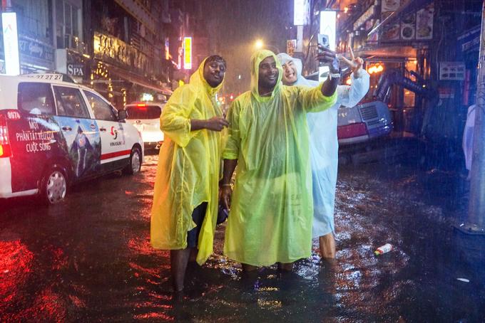 Tourists enjoy heavy downpours, flooding in Saigon - 3