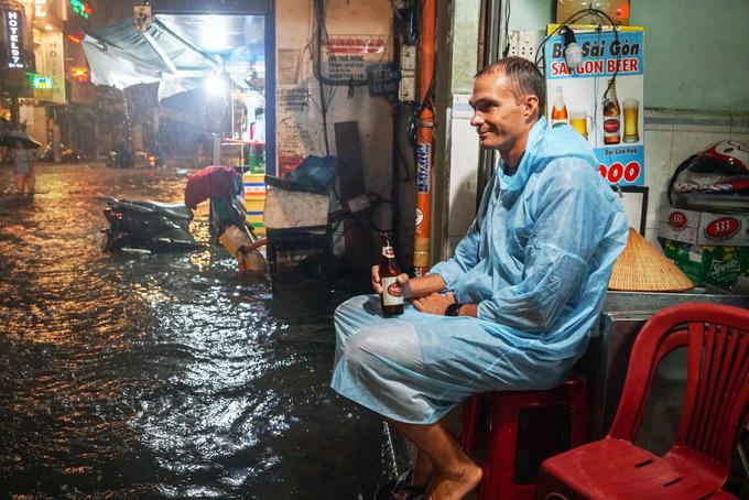 Tourists enjoy heavy downpours, flooding in Saigon - 4