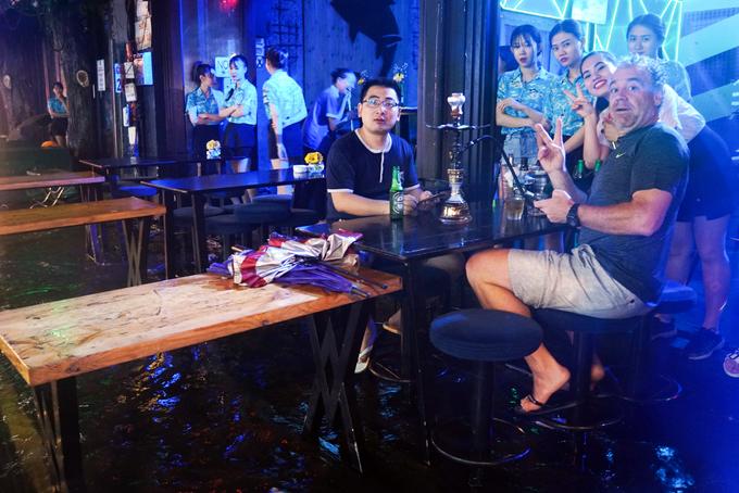 Tourists enjoy heavy downpours, flooding in Saigon - 6
