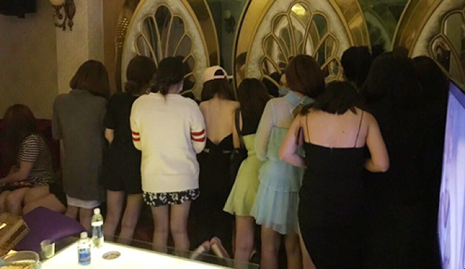 The hotels waitresses were caught playing with drunk customers during police raid. Photo by VnExpress/Quoc Thang