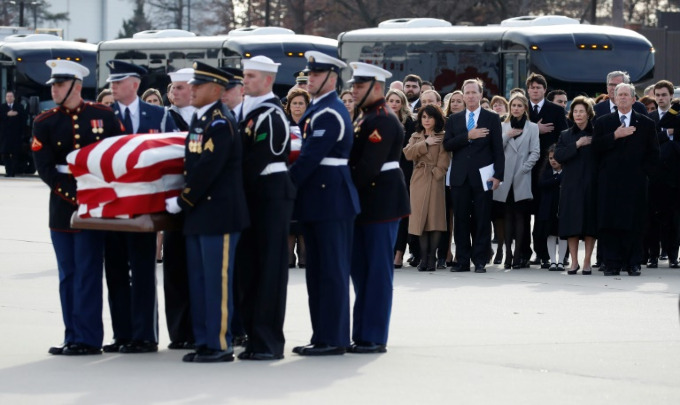 Former US president George W. Bush, Laura Bush and other family members watch as the casket of George H.W. Bush is carried by a military honor guard at Andrews Air Force Base in Maryland, following his state funeral. Photo by POOL/AFP/Alex Brandon