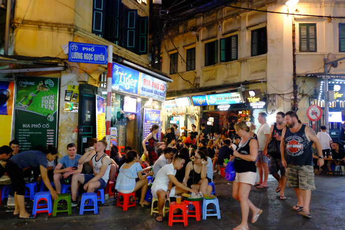 Foreign tourists enjoy beer and food at the intersection of Hanois Ta Hien and Luong Ngoc Quyen streets during the World Cup 2018 season. Photo by VnExpress/Giang Huy