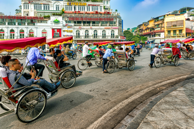 Hanoi old quarter main square, rickshaw drivers carrying tourists around town. Photo by Mark 52/Shutterstock.