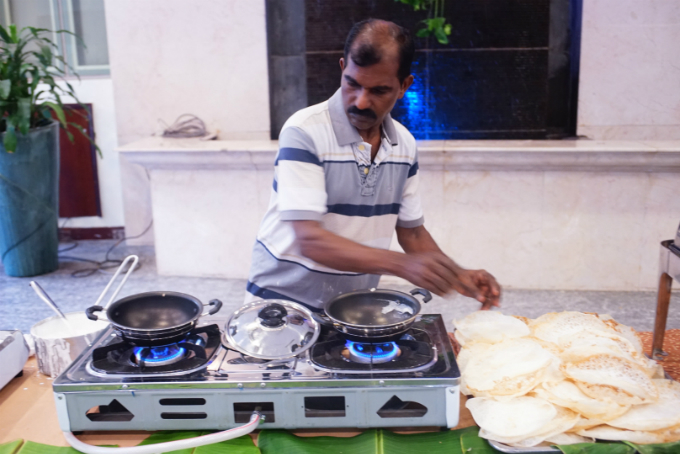 Joy, a chef at Onam@Saigon18. He is the only standing chef at the buffet, making sure everyone receives a hotly made Appam. Appam is an Indian rice cake served with spicy curry.