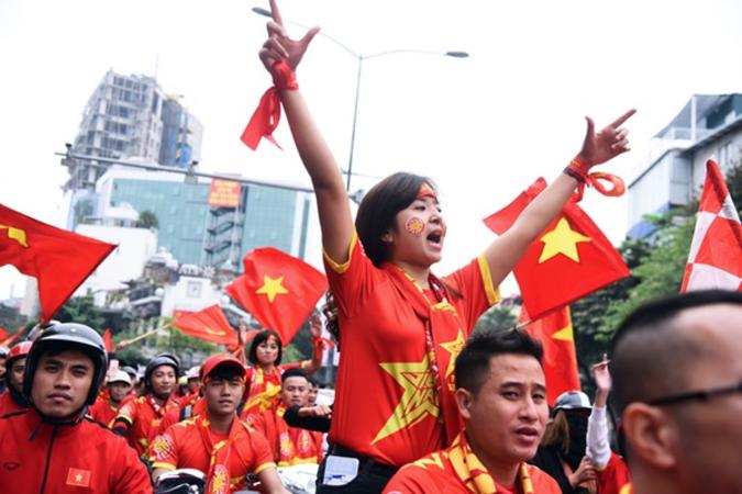 A female Vietnamese fan cheers on a street.