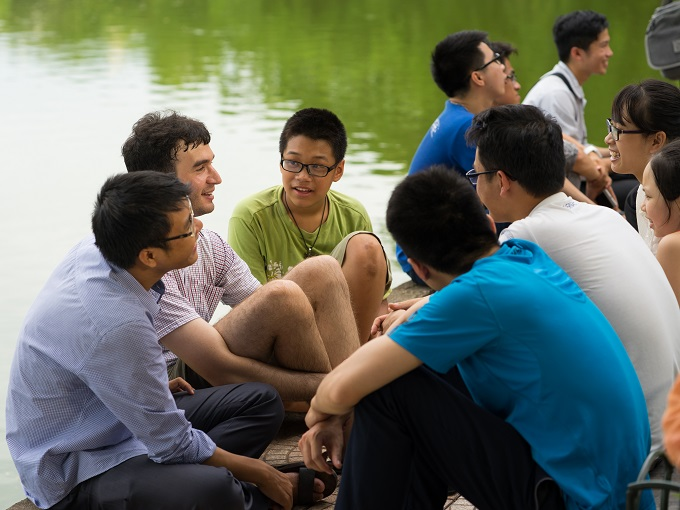 Group of students learn to speak English with English native foreigners at the Hoan Kiem Lake in Hanoi. Photo by Shutterstock/Vietnam Stock Images