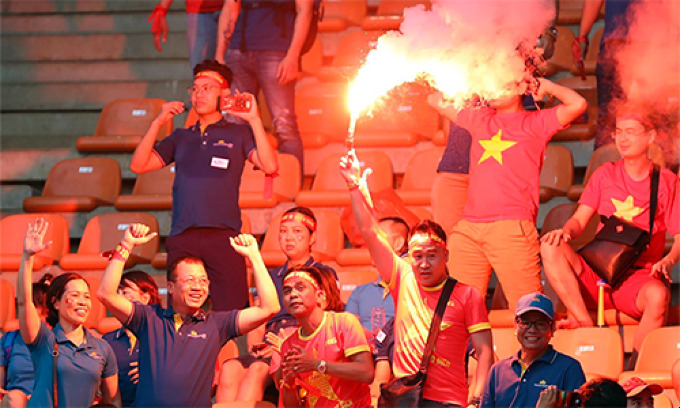 A Vietnamese supporter holds a burning flare at a stadium in Indonesia when Vietnam played against South Korea at the semi-final of Asian Games on August 29. Photo by VnExpress/Duc Dong