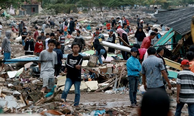 Rescuers and residents look for survivors along the coast in South Lampung on South Sumatra on December 23, 2018, after the area was hit by a tsunami on December 22 following an eruption of the Anak Krakatoa volcano. Photo by AFP/Ferdi Awed