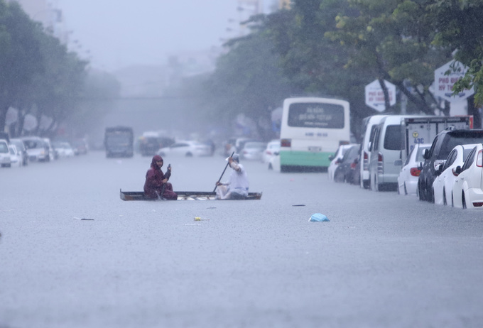 People row a boat across a flooded street in Da Nang on December 9, 2018. Photo by VnExpress/Nguyen Dong