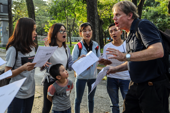 A foreign teacher is teaching English to Vietnamese students of an English center at an open park in HCMC which takes place every Sunday afternoon. Photo by VnExpress/ Thanh Nguyen.