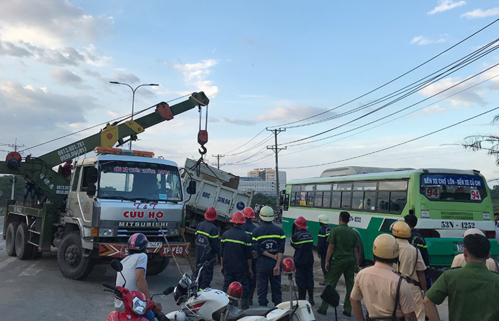 Local authorities use a crane to lift up the fallen truck. Photo by Son Hoa