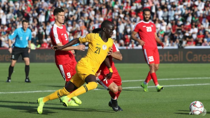 Australias Awer Mabil scores as the Socceroos beat Palestine to keep their hopes of a last 16 place alive. Photo by AFP/Karim Sahib