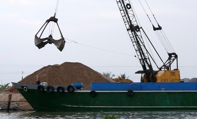 A crane moves sand from a ship on Mekong river in Hau Giang province, Vietnam December 19, 2018. Picture taken December 19, 2018.
