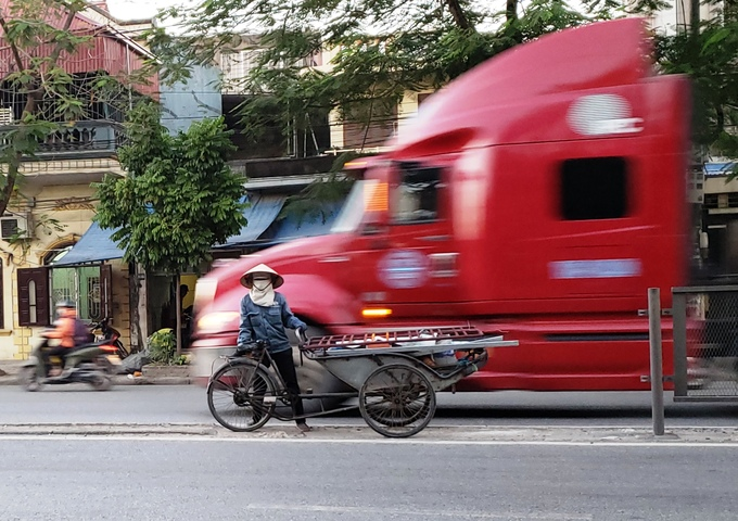 A cyclo driver flirts with danger as a container truck goes past on Nguyen Binh Khiem Street, Hai Phong City. Photo by VnExpress