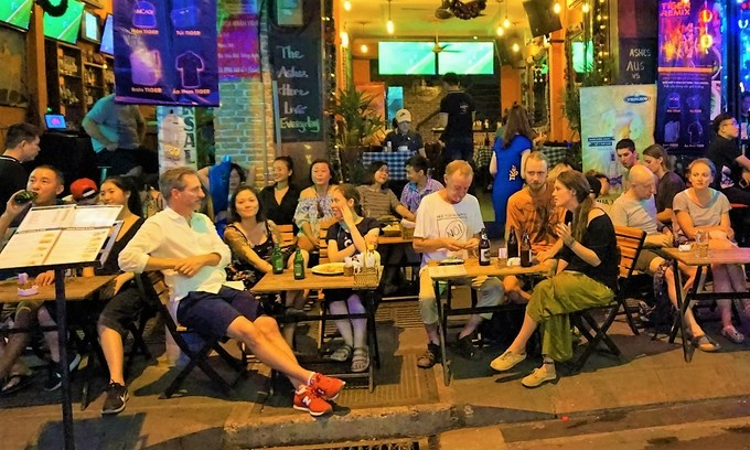 Tourists have food and beer around sidewalk tables of a restaurant in Saigons backpacker street Bui Vien. Photo by VnExpress/Nguyen Quy