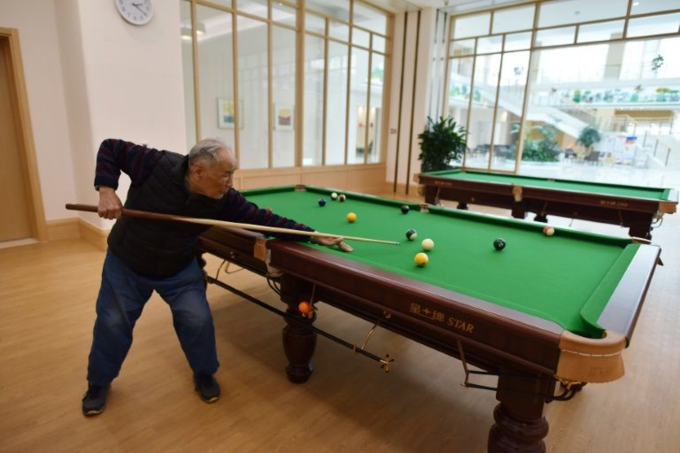 A resident playing pool in a recreation area at the Yanyuan community for senior citizens, on the outskirts of Beijing on December 5, 2018. Photo by AFP/Greg Baker