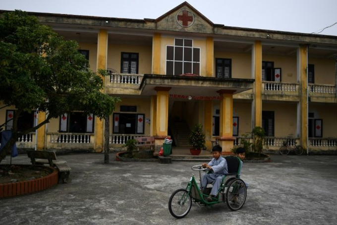 Young Vietnamese boys ride a tricycle for a leprosy patient at the Van Mon Leprosy hospice compound in Thai Binh Province on January 20, 2019. Photo by AFP/Manan Vatsyayana