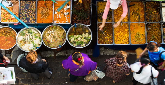 Tourists visit a food stall in Bangkok selling popular Thai street foods. Photo by Shutterstocks/TamDi