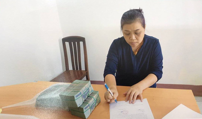 Ton Nu Thi Huyen signs a document at a HCMC police station for allegedly leading a kidney trafficking ring. Photo by Vietnam Television