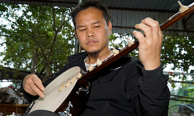 Cuong checks his instruments carefully before handing them over to customers. Photo by Trong Nghia.