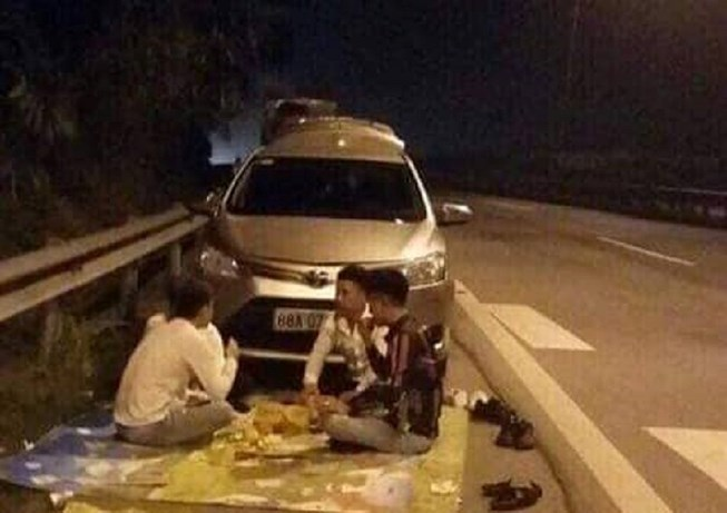 A Facebook photo shows a group of four men have a drinking party on the shoulder of Noi Bai-Lao Cai Expressway on Friday night.