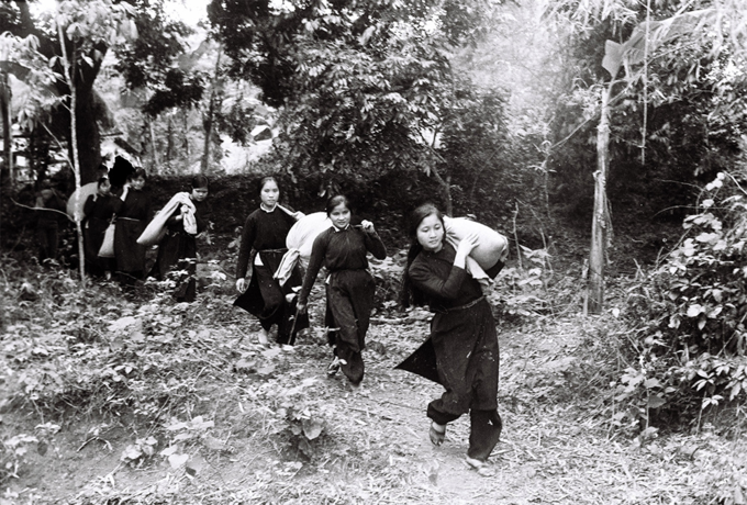 Tay women carry rice up to the hills in Cao Bang Province to support Vietnamese soldiers during the border war in 1979. Photo by Tran Manh Thuong