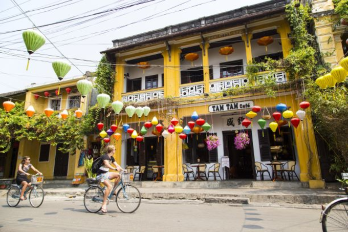 Foreign tourists ride bicycles past typical yellow houses of Hoi An. Photo by Shutterstocks/minhtan