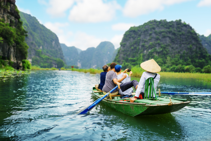 Tourists traveling in boat along the Ngo Dong River and taking picture of the Tam Coc, Ninh Binh, Vietnam. Rower using her feet to propel oars. Landscape formed by karst towers and rice fields. Photo by Shutterstock/Efired.