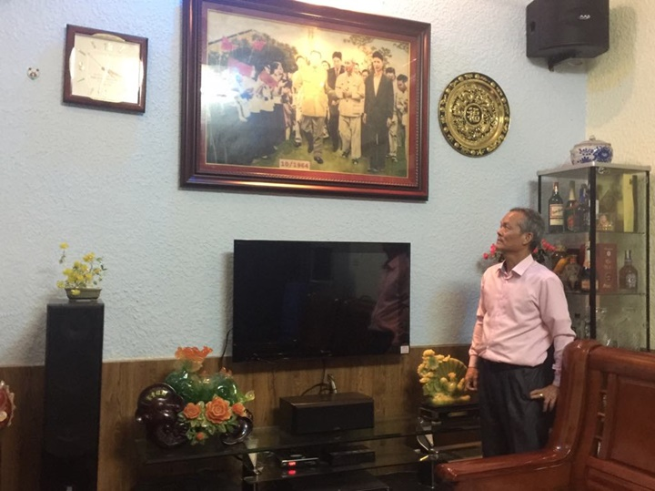 Nguyen Van Hai looks up at the stone picture that emulates the original picture of his father Nguyen Van Vuong welcoming Kim Il Sung and President of Ho Chi Minh in his family's living room.
