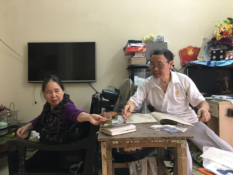 Le Ngoc Tuc (right) and his wife look for the photos taken in North Korea at their home in Thanh Hoa City, Northern Vietnam. Photo by Hanh Pham.