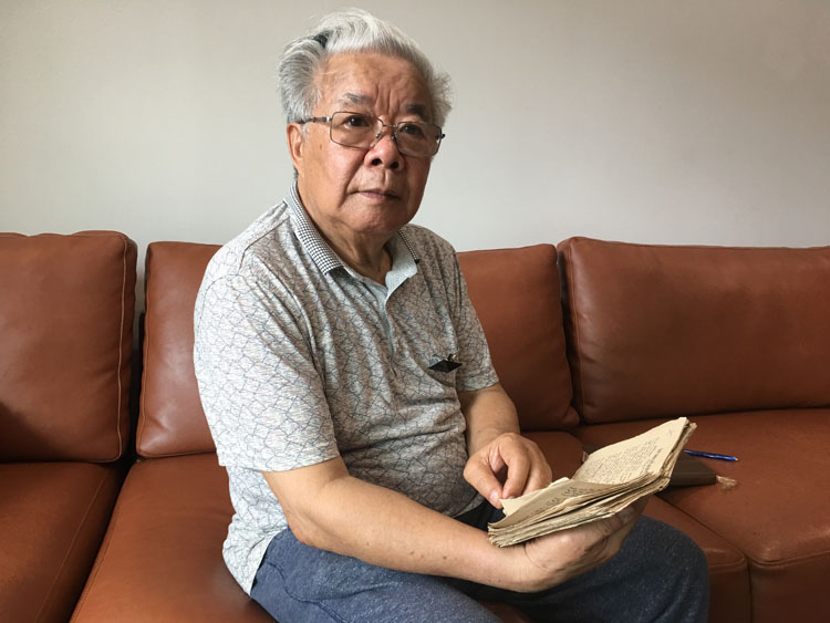 Nguyen Quang Thuyet holds a poetry book in his hand containing his original compositions inspired by all the memories he made in North Korea. Photo by Hanh Pham.