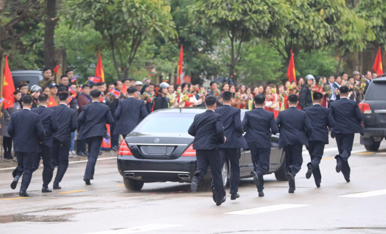 The bodyguards run alongside the car for around 30 meters. Photo by VnExpress/Huu Khoa-Giang Huy