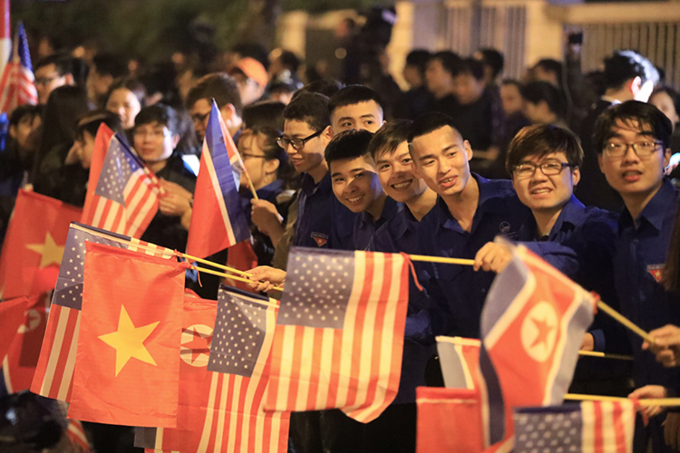 Young people wave flags, of North Korea, U.S. and Vietnam, on the street in Hanoi, February 26, 2019 as they welcome U.S. President Donald Trump coming for the second summit with North Korean leader Kim Jong-un. Photo by VnExpress/Huu Khoa