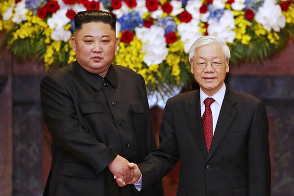 North Korea Chairman Kim Jong-un and President Nguyen Phu Trong shake hands before a conference in Hanoi on Friday. Photo by Giang Huy