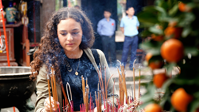 A foreign woman burns incense at Chu Dong Tu Temple in the northern province of Hung Yen. Photo by VnExpress/Phong Vinh