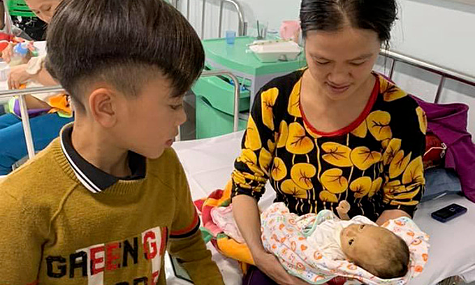 Vi Quyet Chien sits by his mother and youngest brother at Vietnam National Childrens Hospital in Hanoi.