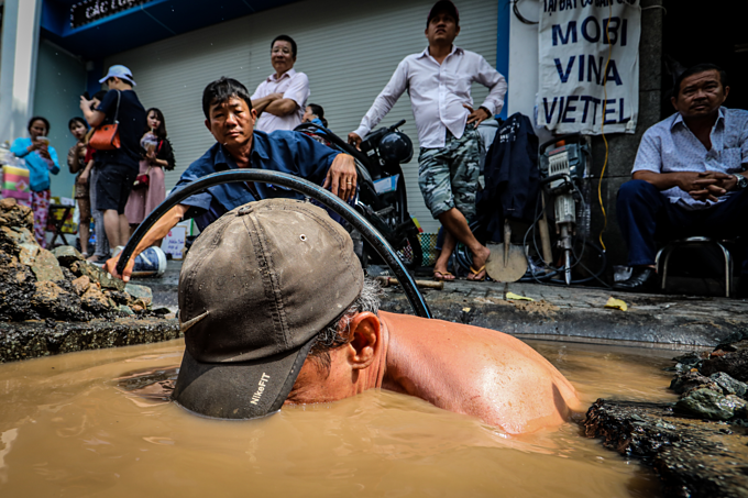Saigon's sons of the soil repair pipes in muddy waters