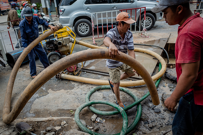 Saigon's sons of the soil repair pipes in muddy waters - 2