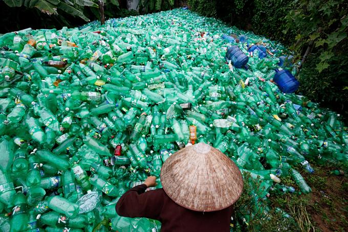 A woman sorts out recyclable plastic soft drink bottles at Xa Cau Village, outside Hanoi, Vietnam. Photo by Reuters/Kham