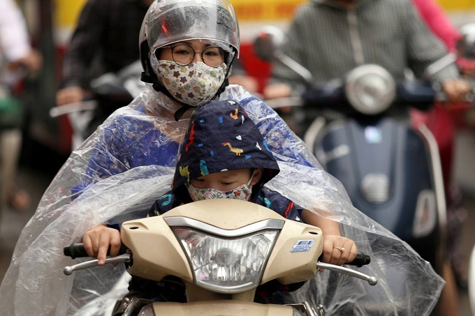 A woman drives her son to school on Hanois Nguyen Trai Street in the morning of April 16, 2019. Banning motorbikes in Vietnam can prevent the not-so-rich community from job and other opportunities. Photo by VnExpress/Gia Chinh