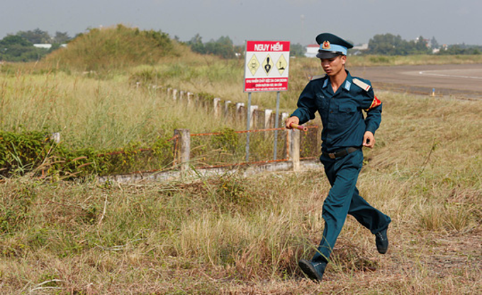A Vietnamese soldier runs past a Danger site at Bien Hoa Airport in Dong Nai Province. Photo by Reuters