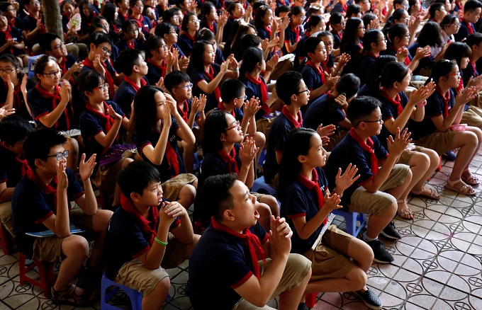 Vietnamese students attend the annual new school year ceremony at a secondary school in Hanoi, Vietnam, September 5, 2018. The building of moral values need to start at young ages. Photo by Reuters/Kham