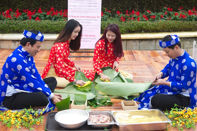 Tourists try to make Vietnamesesticky rice cake in Sun World Ba Na Hills during Tet holiday