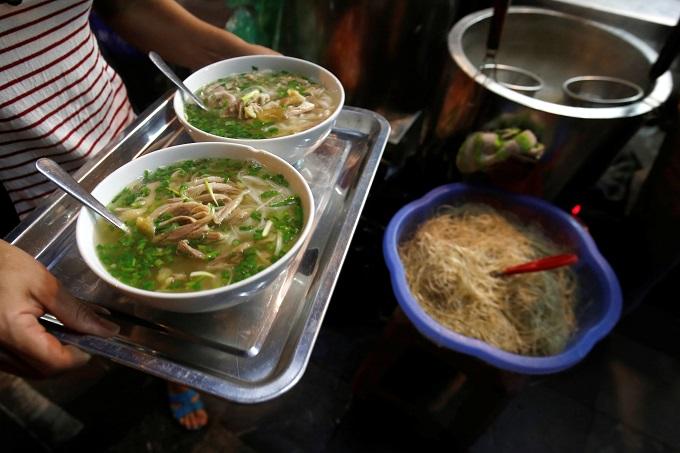 A woman carries bowls of Vietnamese chicken noodle soup phoat a restaurant in Hanoi, Vietnam. Photo by Reuters/Kham