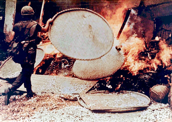 An American soldier throws bamboo sieves into the fire of burning houses during the My Lai massacre on March 16, 1968. Photo courtesy of Ronald L. Haeberle