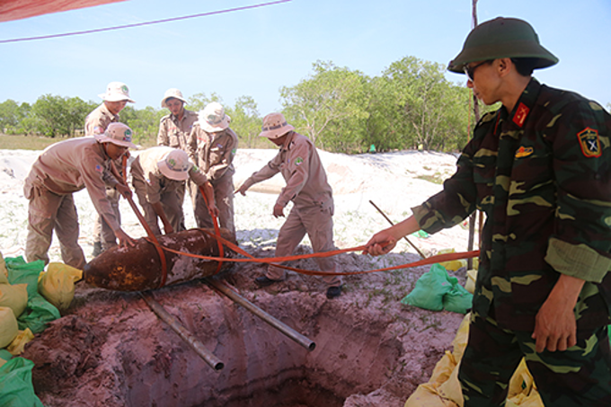 A team from Project RENEW prepares to place a bomb down a hole for disposal in Quang Tri Province, June 4, 2019. Photo by VnExpress/Hoang Tao.