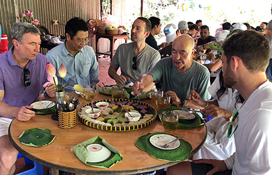 British billionaire Joe Lewis and his entourage enjoy traditional cakes in the Mekong Delta. Photo by VnExpress/Cuu Long