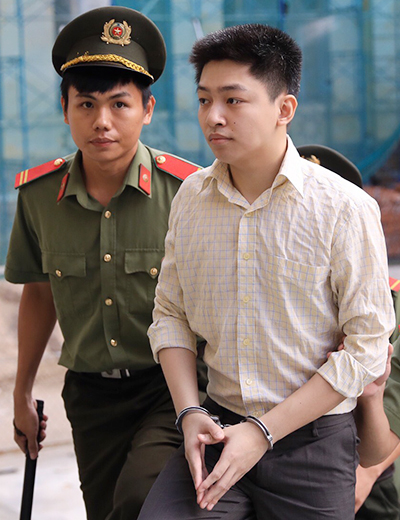 Police take Huynh Duc Thanh Binh to the trial in HCMC, June 24, 2019.