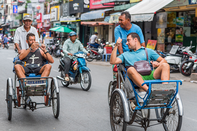 Foreign tourists take cyclo rides in downtown HCMC. Photo by Shutterstock/Hoang Phong